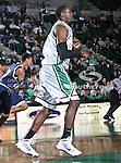 North Texas Mean Green forward George Odufuwa (4) pass the ball off  in the NCAA  basketball game between the Florida International University Panthers and the University of North Texas Mean Green at the North Texas Coliseum,the Super Pit, in Denton, Texas. UNT defeated FIU 87 to 77