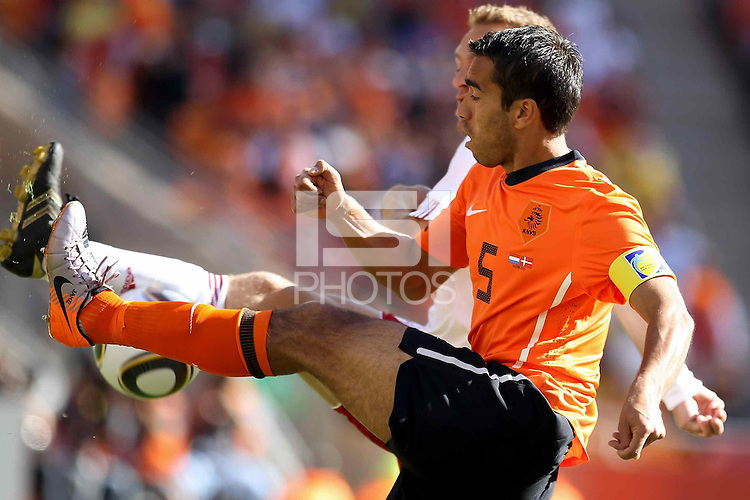Giovanni van Bronckhorst of Holland and Dennis Rommedahl of Denmark battle for the ball.