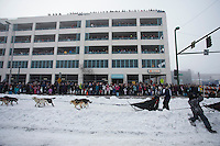 Cindy Gallea runs down 4th avenue as spectators line the parking garage to watch during the ceremonial start of the Iditarod sled dog race Anchorage Saturday, March 2, 2013. ..Photo (C) Jeff Schultz/IditarodPhotos.com  Do not reproduce without permission