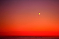 Scenic view of a golden crescent moon as it rises over the Pacific Ocean at sunset.
