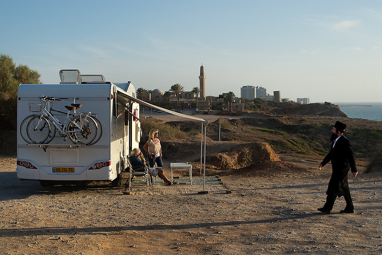 An Ultra-Orthodox Jewish man walks by travellers with their caravan, as worshippers gather for a 'Tashlich' ritual along the Mediterranean Sea in Herzliya, central Israel. 'Tashlich' ('to cast away') is a Jewish practice by which believers go to a flowing body of water and symbolically 'throw away' their sins, before the Day of Atonement ('Yom Kippur'), the holiest day in the Jewish calendar.