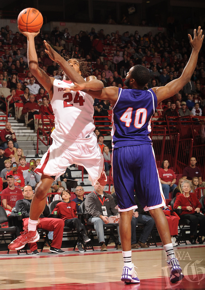 NWA Media/ANDY SHUPE - Arkansas' Michael Qualls (24) and Northwestern State's Marvin Frazier (40) get tangled up beneath the basket during the second half of the Razorbacks' 100-92 win Sunday, Dec. 28, 2014, in Bud Walton Arena in Fayetteville.