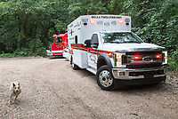 NWA Democrat-Gazette/CHARLIE KAIJO Bella Vista Fire-EMS vehicles drive to the site of a shooting situation, Friday, July 5, 2019 near a media staging area on the intersection of Crossover Rd and Gorden Hollow Rd in Gravette. <br /> <br /> Police responded to a shooting situation that left four people dead in an apparent murder suicide on a nearby property. All four people are related or lived at the residence. One body was found on the driveway. Authorities do not believe there is a danger to the public.