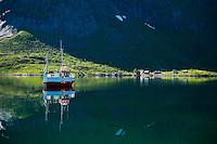 Reflection of moored boat against cliff, Vindstad, Moskenesoy, Lofoten islands, Norway