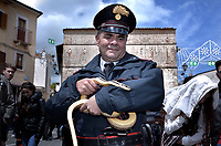 """the police officer of Cocullo with snakes in hand before the procession.The feast of snakes. Process dedicated to the Saint Dominic, in the streets of Cocullo, in the Abruzzo region, Italy on May 1, 2019.<br /> <br /> <br /> <br /> The St. Domenico's procession in Cocullo, central Italy. Every year on the first  of May, snakes are placed onto the statue of St. Domenico and then the statue is carried in a procession through the town. St. Domenico is believed to be the patron saint for people who have been bitten by snakes:<br /> <br /> Italy, Cocullo, in the Province of L'A...quila, is at 870 meters a.s.l., along the railway line connecting Sulmona to Rome. The village rises alongside Mount Luparo (1327 meters) """"The valley opening in front of the village is surrounded by bare rocks, while on the other side, to the south, snow-capped mountain crests follow one after the other...""""<br /> San Domenico Abate lived in the 10th and 11th centuries AD. Born in Foligno, in the Umbria region, he started his pilgrimages, preaching and ascetic practices in Central Italy, making miracles recorded by the word-of-mouth tradition. He died on 22 January 1031 and was buried in Sora.<br /> <br /> Cocullo snake charmers are over with their snake hunting. They proceeded through the During the procession on the first in May, before the snakes are placed all over the statue of St. Dominick, they will be fed with milk kept in containers with crusca. It is the snake that, most of all other elements, expresses an ancestral myth: the unknown aspect and unpredictability of the natural environment with man's innate need to achieve the dominance on his own habitat. <br /> <br /> Snakes and wolves were the emblems of Italic peoples like the Marsians and Irpinians. Some areas in Abruzzo, especially in the Sagittario valley, were under the menace of wolves and snakes, which for the local populations represented the uncertainty and anxiety of their existence that, together with the precariousness and """