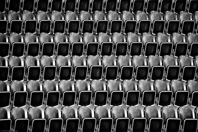 The abstract photograph of stacked rows of seats in a stadium.