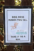 Sign made by the children warning of the dangers from dog mess and hung on the school fence, Primary school, Surrey.
