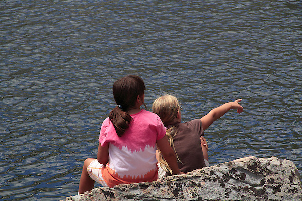 Girls sitting along mountain lake, Boulder, Colorado.