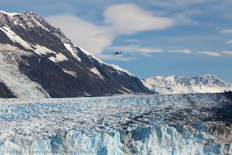 Bush plane flies over Cascade glacier,  Barry Arm, Prince William Sound, southcentral, Alaska.
