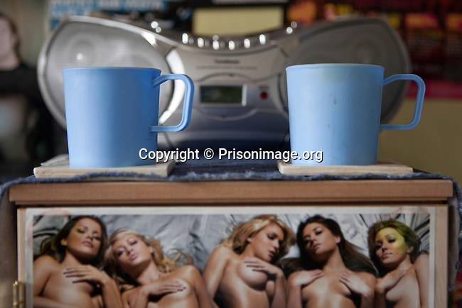 Plastic cups issued to prisoners and a picture of semi-nude women inside an 'enhanced' prsoners room on H wing at the Young Offenders Institution  in Aylesbury, United Kingdom.  Under the Incentives and Earned Privilege Scheme, prisoners in the U.K. can earn extra privileges for good behaviour such as wearing their own clothes, having televisions in their cells, and having more free time to socialise.  They are often housed together in their own wing.  There are three levels of earned privileges - Basic, Standard and Enhanced.
