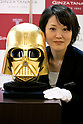 A member of staff poses for a picture with a gold plated Darth Vader mask at the Ginza Tanaka jewelry store on April 22, 2015, Tokyo, Japan. The jewelry store will sell a series of Star Wars themed golden coins from May 4th 2015 through to April 30, 2016, to commemorate the new Star Wars movie Episode VII The Force Awakens which is scheduled for release on December 18, 2015. Four kinds of 24k gold coins each with an individual with serial number will be sold with prices ranging from 500 USD to 8,000 USD. (Photo by Rodrigo Reyes Marin/AFLO)
