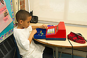 MR / Schenectady, NY. Zoller Elementary School (urban public school). Kindergarten inclusion classroom. Student (boy, 6, African American & Puerto Rican American) plays with toy cash register at free playtime. Marbles are used to symbolize money. MR: Car38. ID: AM-gKw. © Ellen B. Senisi.