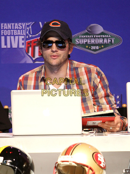 ASHTON KUTCHER. Fantasy Football Superdraft at the Palms Resort Hotel and Casino, Las Vegas, Nevada, USA. .27th August 2010.half length plaid white checked shirt red blue baseball cap hat sunglasses shades apple mac computer laptop .CAP/ADM/MJT.© MJT/AdMedia/Capital Pictures.