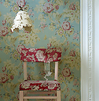 The floral pattern of the loose covers on this simple chair reflects a different colour way to the chintz wallpaper