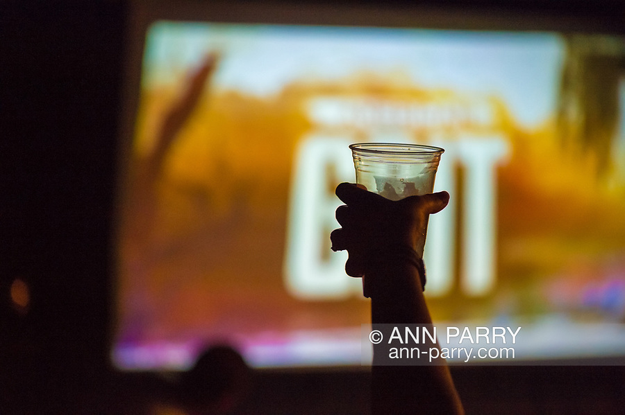 """Merrick, New York, USA. 11th June 2017.  At a Viewing Party for the premiere of """"American Grit"""" Season 2, a woman guest cheers and holds up a plastic drink cup then silhouetted in front of large TV, in backyard of contestant Chris Edom. Edom family hosted neighborhood party during broadcast of that episode of the FOX network reality television series."""