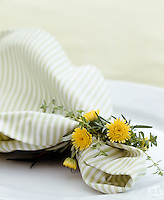 Detail of a napkin tied with tiny yellow chrysanthemums and sprigs of rosemary and thyme