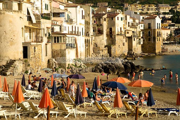 Sun bathers on beach at Cefalu, Sicily, Italy