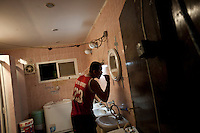 Qatar - Doha - A  worker brushing his teeth in the bathroom of a labour camp in the industrial area of Doha.