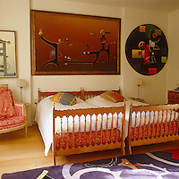 Paintings by Roger Nellens hang on the walls of his bedroom