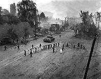 A U.S. Marine tank follows a line of prisoners of war down a village street.  September 26, 1950.  S. Sgt. John Babyak, Jr.  (Marine Corps)<br /> NARA FILE #:  127-N-A3810<br /> WAR & CONFLICT BOOK #:  1488