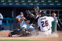 Northwest Arkansas Naturals infielder Emmanuel Rivera (26) safely slides into home for a run ahead of the tag from Arkansas Travelers catcher Joseph Odom (5) during a Texas League game between the Northwest Arkansas Naturals and the Arkansas Travelers on May 30, 2019 at Arvest Ballpark in Springdale, Arkansas. (Jason Ivester/Four Seam Images)