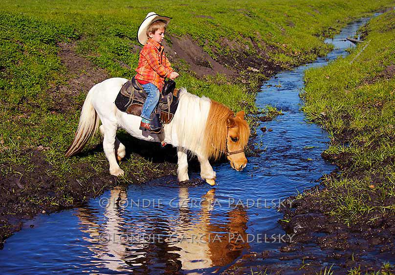 Young cowboy riding pony across the creek. San Luis Obispo, California