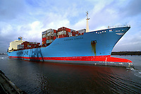 A profile view of a cargo ship from the Maersk shipping line transporting containers on deck as it departs from port.