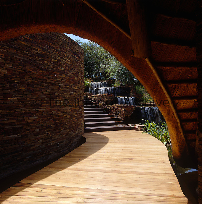 A curved wall of packed shale emphasises a sinuous wooden walkway and waterfall at the spectacular entrance to Leadwood Lodge