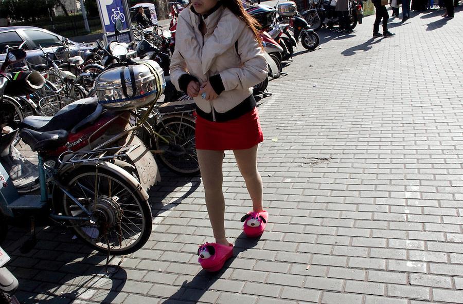 A woman walks in her slippers in Shanghai.