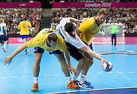 31 JUL 2012 - LONDON, GBR - Chris McDermott (GBR) of Great Britain (centre, in white, blue and red) tries to catch a rebounded ball during the men's London 2012 Olympic Games Preliminary round handball match against Sweden at The Copper Box in the Olympic Park, in Stratford, London, Great Britain .(PHOTO (C) 2012 NIGEL FARROW)