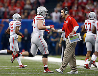 Ohio State defensive coordinator Luke Fickell gives defensive lineman Joey Bosa (97) a fist bump after a defensive stop during the first quarter of the Allstate Sugar Bowl college football playoff semifinal against the Alabama Crimson Tide at the Mercedes-Benz Superdome in New Orleans on Jan. 1, 2015. (Adam Cairns / The Columbus Dispatch)