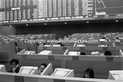 """The Peoples Republic of China. Shanghai. 2000. """"Red vests"""" on the trading floor of the Shanghai Stock Exchange building in Pudong, which opened late 1997.  The biggest in mainland China, the stock exchange was only established in Shanghai in 1990 but now has over 600 listed companies and the market is value number two in the Asia Pacific region.  It is government policy to encourage people to be involved in stock market as many quoted companies are state-owned, or former state-owned, and badly in need of capital.."""
