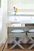 A bold black and white patterned fabric with a contrasting green piping has been used to upholster a pair of stools on the stiarcase landing