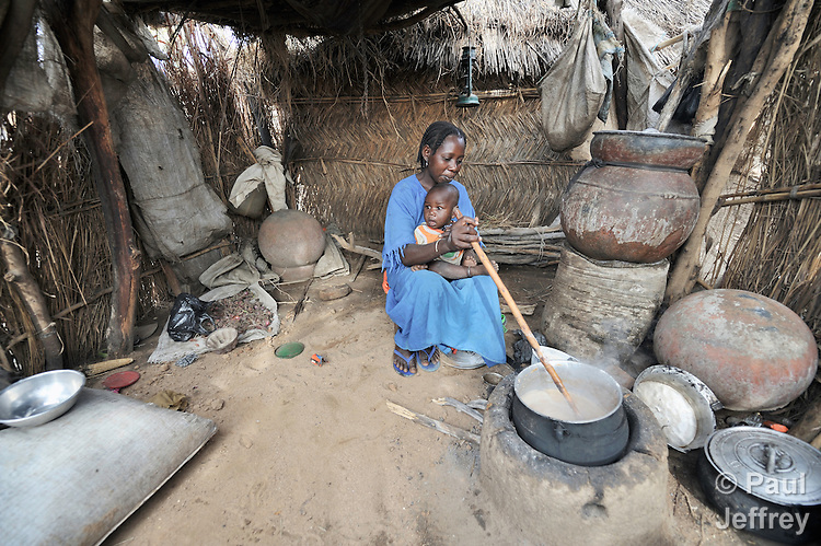 A woman cooks a meal in her hut in the Goz Amer refugee camp in eastern Chad. More than a quarter million residents of Darfur live in camps in Chad, along with almost 200,000 Chadians who have been internally displaced by related violence.