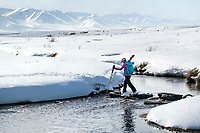 A woman skier crosses a creek while ski touring in the Suusamyr region of Kyrgyzstan