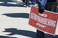 "Washington, DC - March 26, 2019: A person holds an ""End Gerrymandering"" sign outside the U.S. Supreme Court, March 26, 2019. The Court heard oral arguments in the cases of Rucho vs Comon Cause and Lamone vs Benisek, dealing with partisan gerrymandering.  (Photo by Lenin Nolly/Media Images International)"