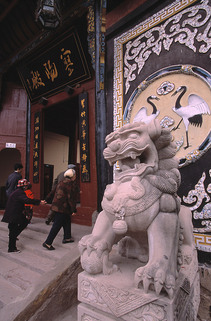 Tourists walk past mythical symbols while entering Ming Shan temple in old Fengdu China