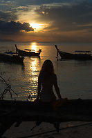 Silhouette of a girl sitting on a fallen tree on the beach, Ko Lipe, Thailand