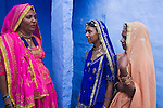 Rajasthani women in traditional clothes in front of house in Blue City (old town); the blue houses were originally for Brahmins but non-Brahmins soon joined in, as the colour was said to deflect the heat and keep mosquitoes away, Jodphur, Rajasthan, India --- Model Released