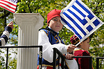 Greek Parade in New York City. A boy in traditional clothes, holds a flag on a float in the Greek Parade in New York City.