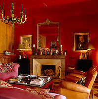 This red sitting room is furnished with a pair of leather armchairs and pink sofas with gilt-framed paintings and a mirror on the walls