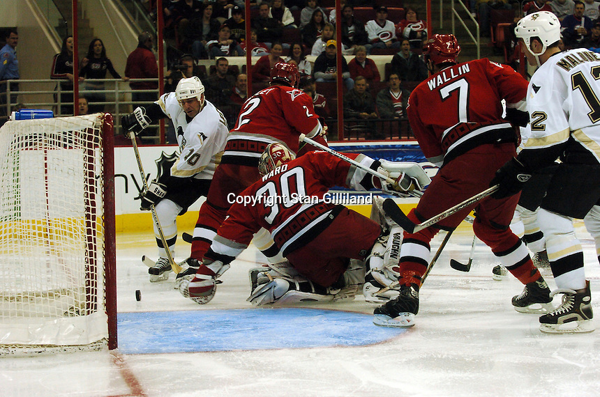 The Pittsburgh Penguins' John Leclair tries to gain control of a puck headed into the crease despite the efforts of Carolina Hurricanes' Glen Wesley (2), Niclas Wallin (7) and goaltender Cam Ward (30) in Raleigh, NC Friday, February 10, 2006. The Penguins won the game 4-3.