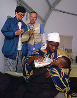 Sister Terry Shields, RN., Bryn Mawr, Penn., left, Dr. Doyt, Conn., Rochester, Minn., confer while a mother gives a medicine and formula mixture to her ill child in an inpationt tent in the AmeriCares clinic in Buranga, Rwanda, October 1994. The New Canaan Connecticut humanitarian organization set up their clinic on the road between Goma, Zaire (now Congo) and Kigali, Rwanda to help refugees returning from the camps in Goma and the people living in the area whose illnesses resulted from the destruction of what little infrastructure existed before civil war. (photo Rick D'Elia)