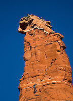Three rock climbers ascend a sandstone rock formation called Kachina Woman near Sedona, Arizona