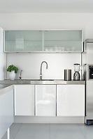 In the clean, sleek kitchen, the combination of white lacquer, frosted glass and stainless steel is both stylish and practical.