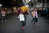 SAO PAULO, 21 DE JULHO 2012- COTIDIANO-  Senhora é vista caminhando no centro de Sao Paulo, na frente do Teatro Municiapal com fardo de laranja na cabeça.<br /> <br /> FOTO VAGNER CAMPOS BRAZIL PHOTO PRESS
