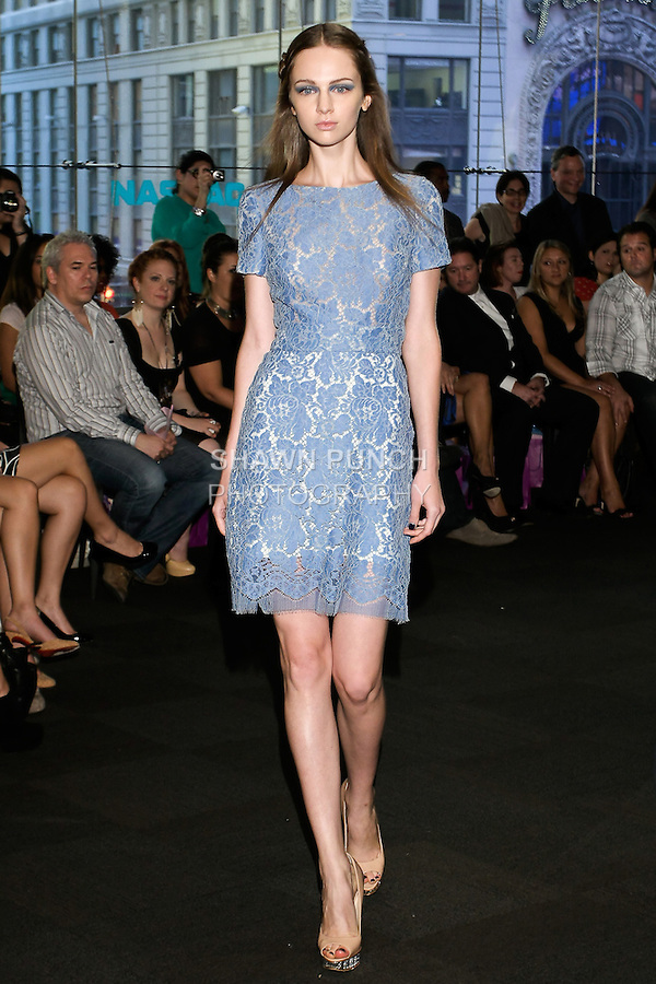 "Model walks runway in a short sleeve light blue lace dress, from the Yuna Yang Spring Summer 2013 ""Close your eyes and see the world"" collection, at the NASDAQ Marketsite, during New York Fashion Week, on September 7, 2012."