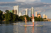 Vibrant and attractive fun couple on stand up paddle board surfboard surfing together on Lady Bird Lake on a hot summers day in Austin, Texas.