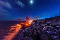Visitors view the spectacular sight of lava flowing down a cliff and into the ocean on a starry night, Hawai'i Volcanoes National Park, Hawai'i Island.
