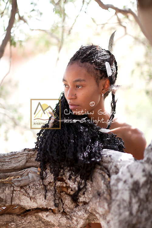 A young woman of the Damara tribe of Namibia stands in the shade of a tree in the central Namib. Her lng hair is adorned with feathers of local birds.